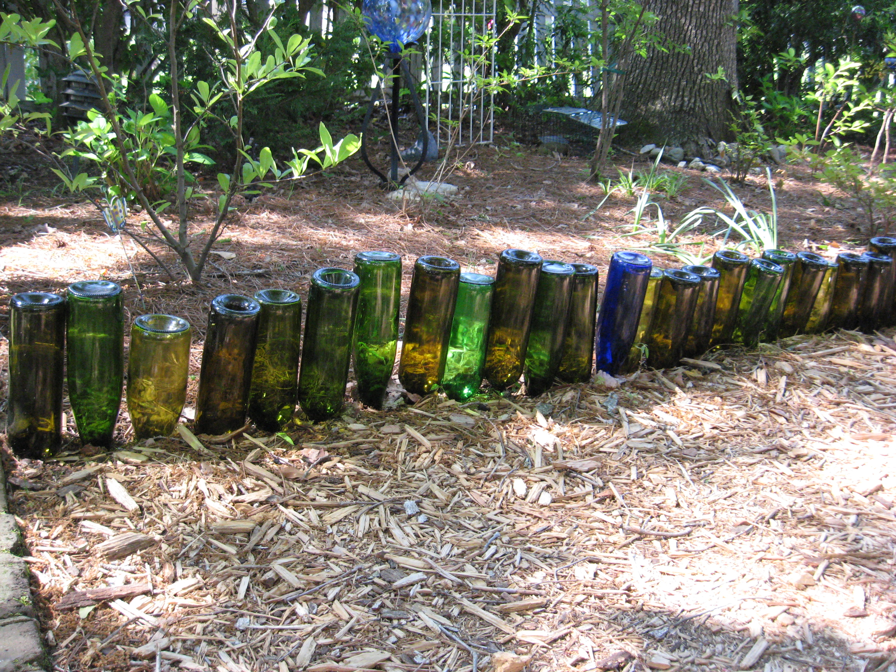 Bottle garden edging cottage in the oaks for How to use wine bottles in the garden